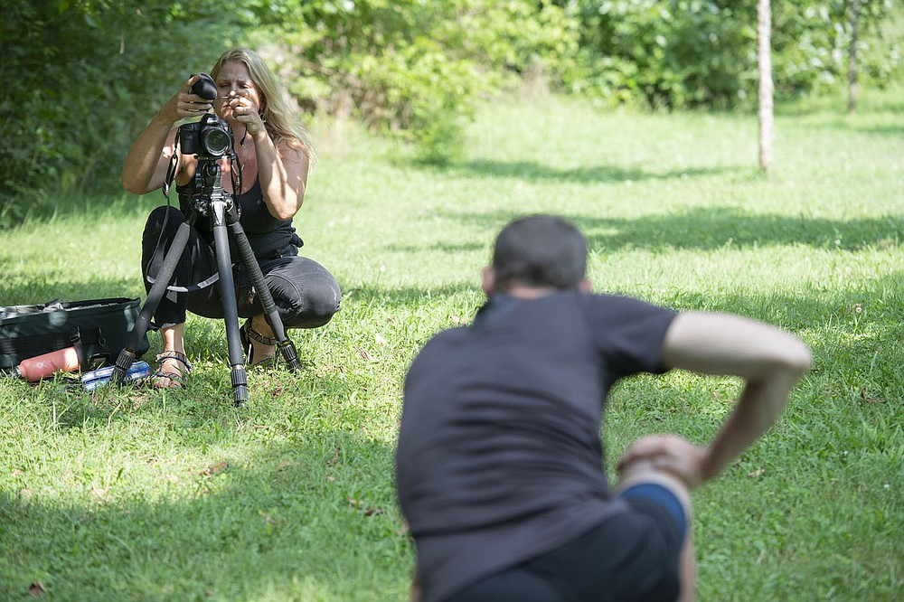 Diana Michelle of Fayetteville sets up her camera to record Paul Summerlin of Fayetteville while he performs some yoga poses Wednesday July 28, 2021 at Wilson Park in Fayetteville. (NWA Democrat-Gazette/J.T. Wampler)