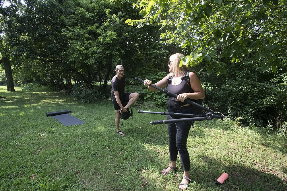 Diana Michelle of Fayetteville sets up to record Paul Summerlin of Fayetteville while he performs some yoga poses Wednesday July 28, 2021 at Wilson Park in Fayetteville. (NWA Democrat-Gazette/J.T. Wampler)