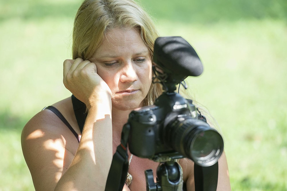 Diana Michelle of Fayetteville keeps her eyes on her camera while recording Paul Summerlin of Fayetteville as he performs some yoga poses Wednesday July 28, 2021 at Wilson Park in Fayetteville. (NWA Democrat-Gazette/J.T. Wampler)