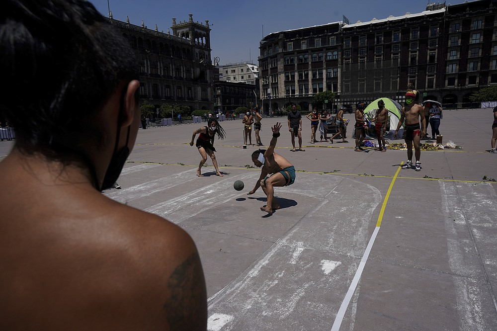 """Dancers play """"Pelota"""" during a performance as part of the commemoration marking the 700 year anniversary of the founding of the Aztec city of Tenochtitlan, known today as Mexico City, at the Zocalo square in Mexico City, Monday, July 26, 2021, amid the new coronavirus pandemic. (AP Photo/Fernando Llano)"""