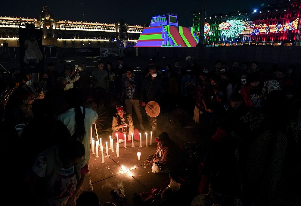 Mexican dancers light a candle during a ceremony to commemorate the 500th anniversary of the fall of the Aztec empire capital of Tenochtitlan, known today as Mexico City, at Mexico City's main square the Zocalo, Friday, Aug. 13, 2021. (AP Photo/Eduardo Verdugo)