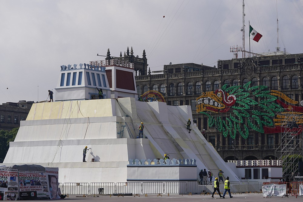 Workers build a replica of the Aztec Templo Mayor, with an image of the Pre-columbian god Quetzalcoatl adorning the surrounding buildings, at Mexico City's main square the Zocalo, Monday, Aug. 9, 2021. Mexico City is preparing for the 500 anniversary of the fall of the Aztec capital of Tenochtitlan, today's Mexico City, on Aug. 13, 2021. (AP Photo/Eduardo Verdugo)