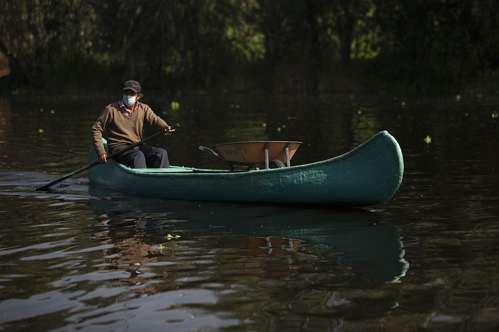 """A farmer carries a wheelbarrow in his canoe as e paddles to his farm known as """"chinampa,"""" in Xochimilco, Mexico City, Thursday, Aug. 12, 2021, as Mexico City prepares for the 500th anniversary of the fall of the Aztec capital of Tenochtitlan. The canals and floating gardens of Xochimilco are the last remnants of a vast water transport system built by the Aztecs to serve their capital of Tenochtitlán. (AP Photo /Marco Ugarte)"""