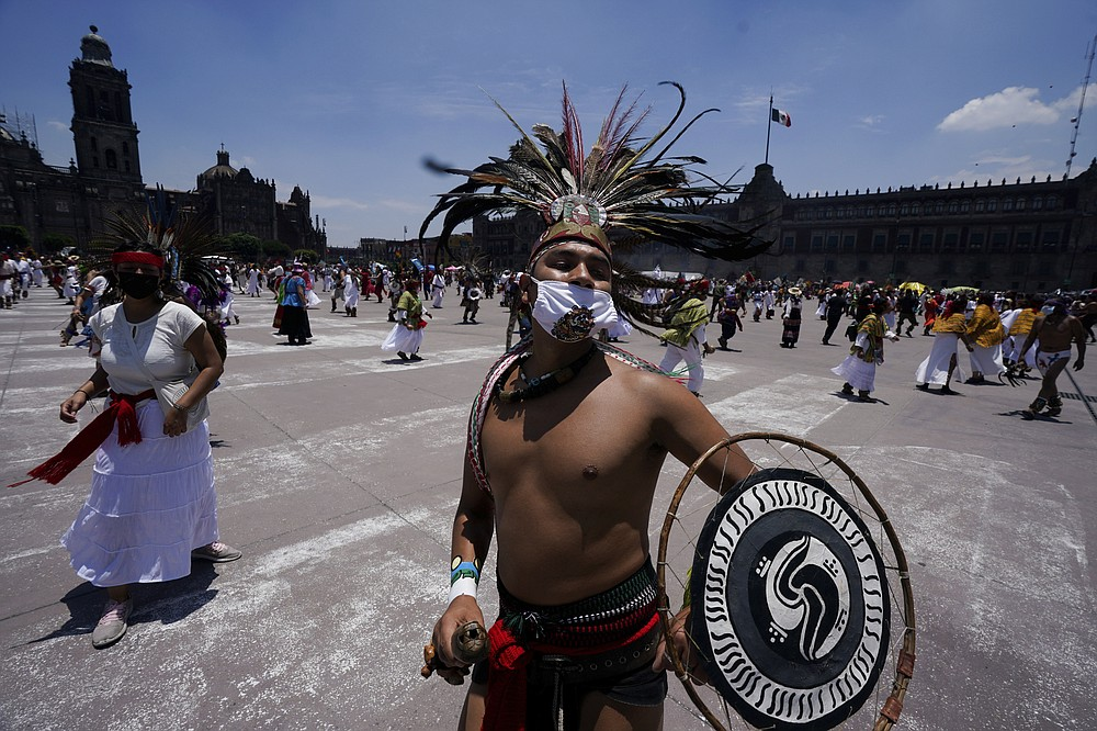 Mexican dancers perform during a ceremony as part of the commemoration marking the 700 year anniversary of the founding of the Aztec city of Tenochtitlan, known today as Mexico City, in Mexico City, Monday, July 26, 2021, amid the new coronavirus pandemic. (AP Photo/Fernando Llano)