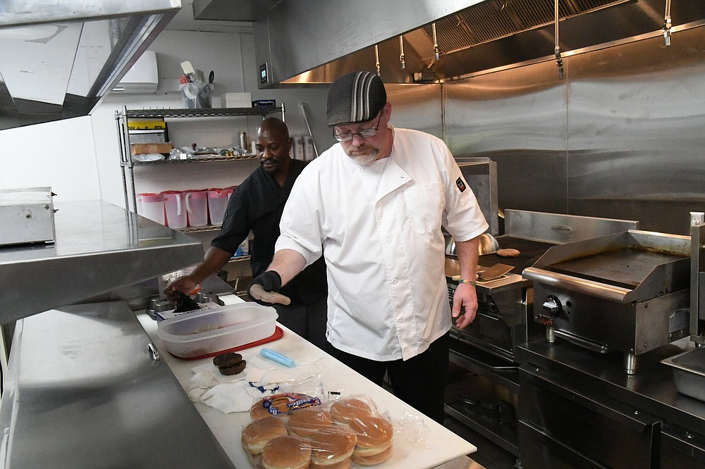 Michael Dampier, Ohio Club kitchen general manager, right, and Adrian Poland, senior head cook, prepare hamburgers in the Ohio Club's new kitchen. - Photo by Tanner Newton of The Sentinel-Record