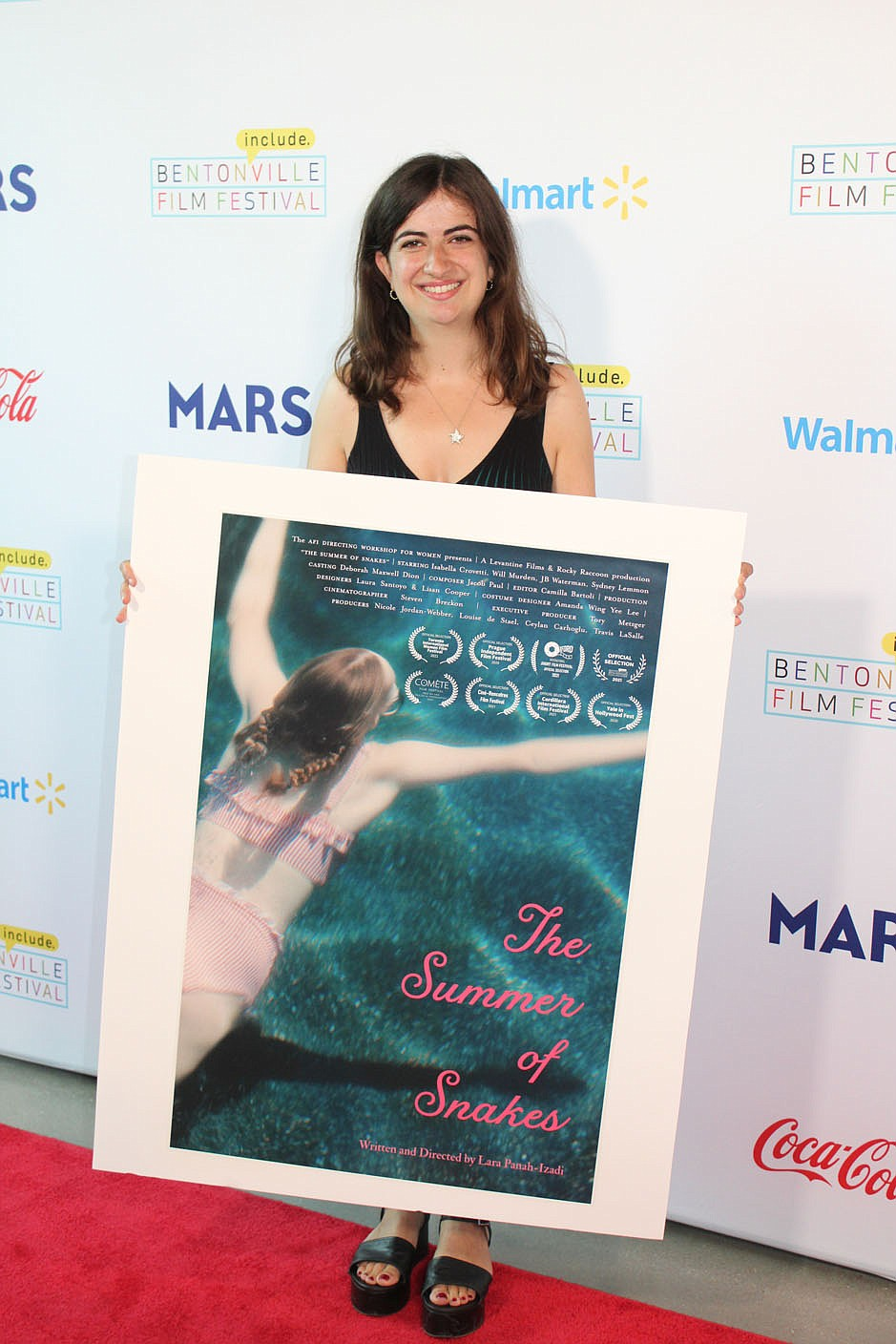 """Director Lara Panah-Izadi stands with a poster of her Bentonville Film Festival entry, """"The Summer of Snakes."""" (NWA Democrat-Gazette/Carin Schoppmeyer)"""