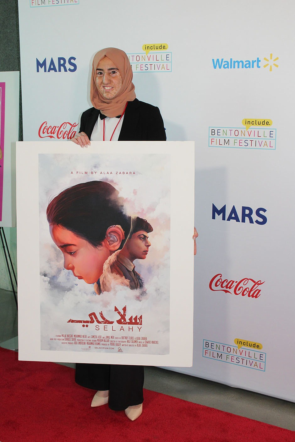 """Writer and director Alaa Zabara  stands with a poster of her Bentonville Film Festival entry, """"Selahy."""" (NWA Democrat-Gazette/Carin Schoppmeyer)"""