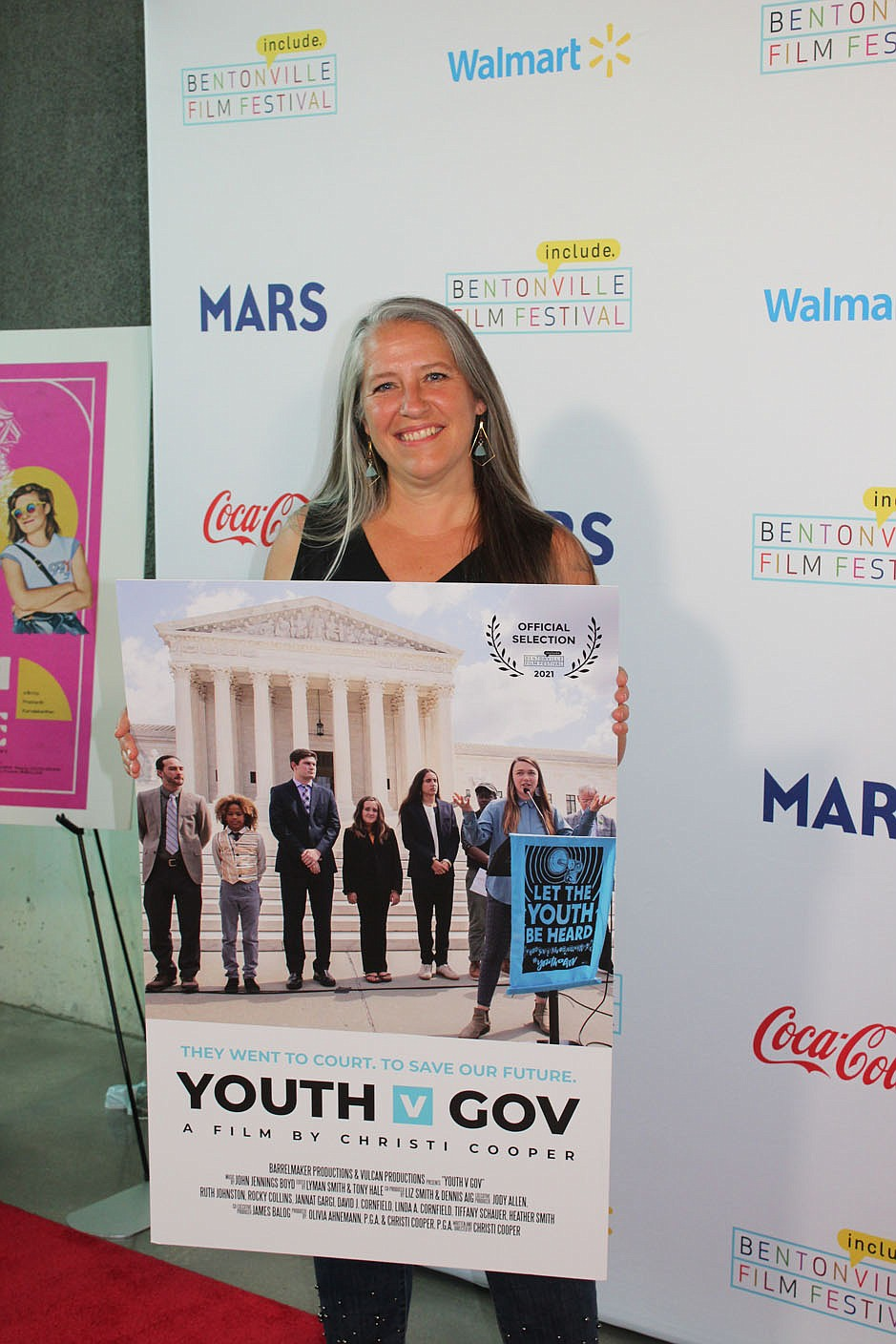 """Writer, director and producer Christi Cooper stands with a poster of her Bentonville Film Festival entry, """"Youth V Gov."""" (NWA Democrat-Gazette/Carin Schoppmeyer)"""