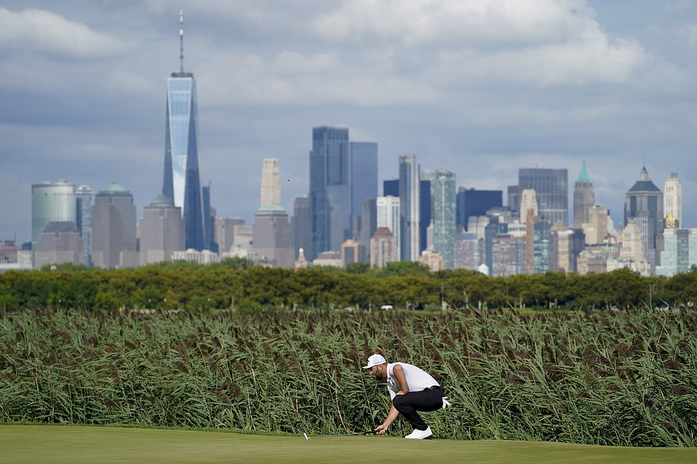 Jon Rahm of Spain reads the 14th green as the Manhattan skyline looms in the distance in the third round of the Northern Trust Golf Tournament, Saturday August 21, 2021, at Liberty National Golf Course in Jersey City, NJ (AP Photo / John Minchillo)