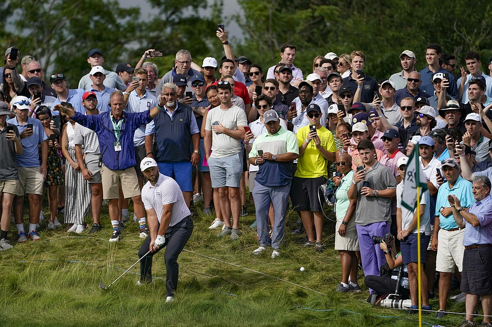 Jon Rahm of Spain hits the rough on the 13th green among spectators in the third round of the Northern Trust Golf Tournament, Saturday August 21, 2021, at the Liberty National Golf Course in Jersey City, NJ (AP Photo / John Minchillo)