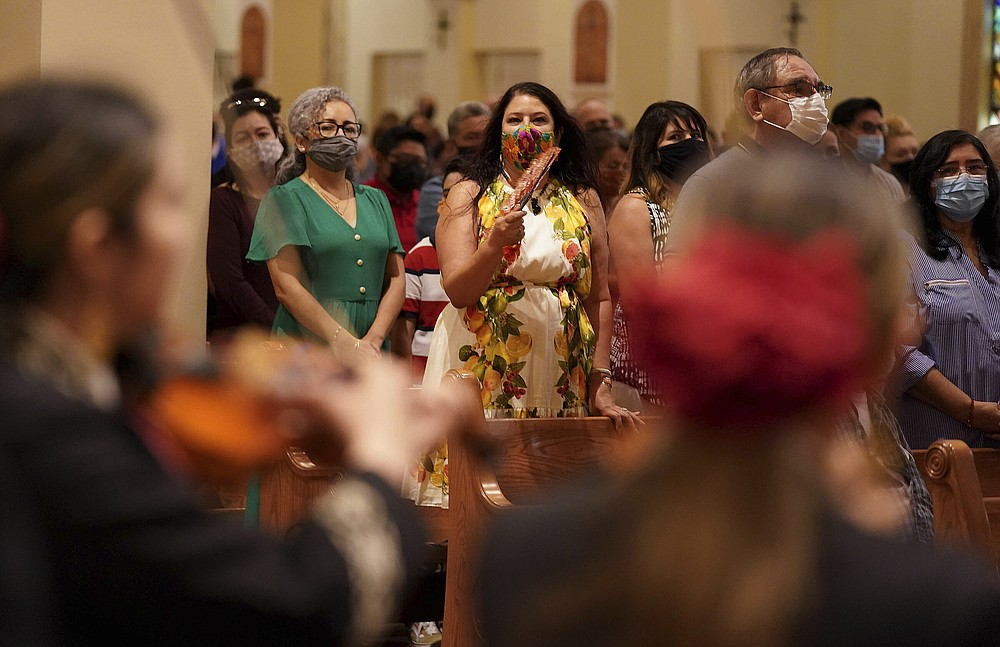 Parishioners of St. Augustine Cathedral watch and listen to mariachi band Los Changuitos Feos (Ugly Little Monkeys) perform for them on Sunday, August 18, 2021 in downtown Tucson.  While mariachi is a popular genre at its core, musicians and parishioners say its emotional interplay between trumpet, violin, guitar, vihuela, and guitarrón is a natural complement to the sacred rites of Mass.  (AP Photo / Darryl Webb)