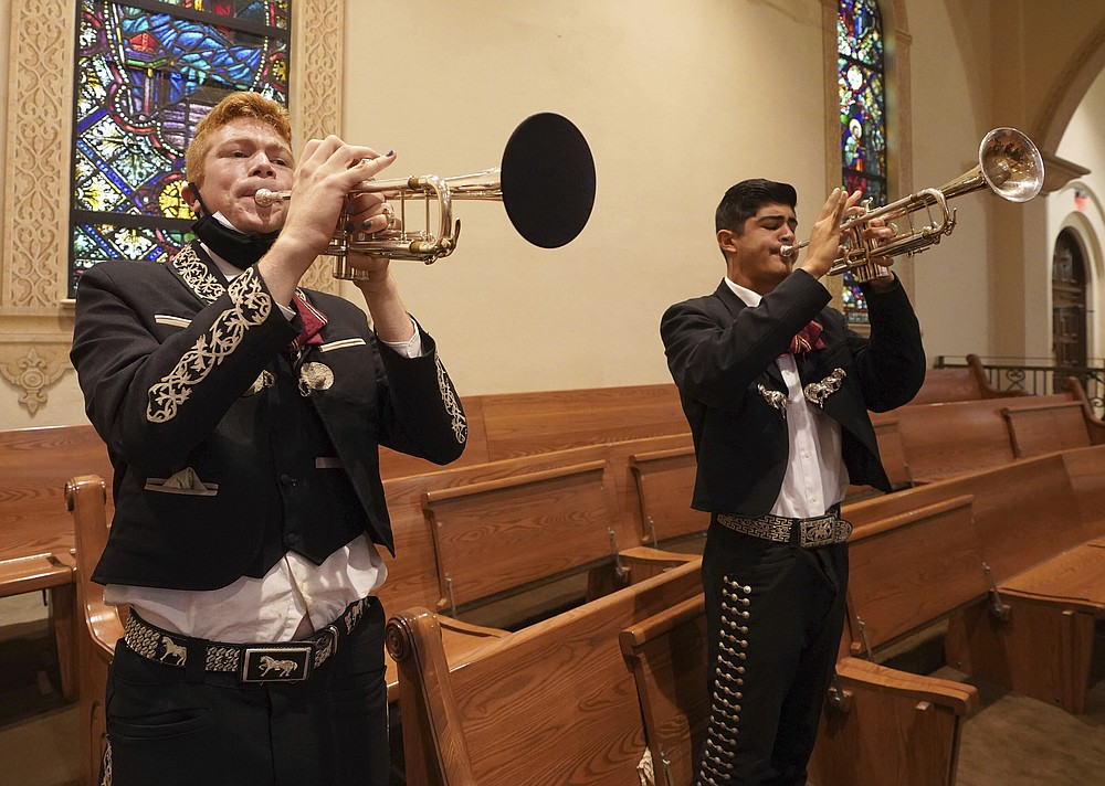Mariachi Los Changuitos Feos (Ugly Little Monkeys) members Cameron Davison 18 and Roman Murillo 14 play their trumpets during morning mass at St. Augustine Cathedral on Sunday, August 18, 2021 in downtown Tucson.  (AP Photo / Darryl Webb)
