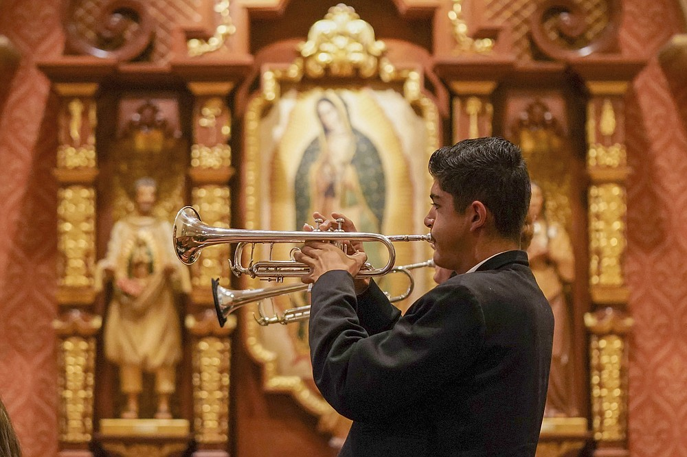 Los Changuitos Feos (Ugly Little Monkeys) mariachi band members Roman Murillo 14, and Cameron Davison 18, play their trumpets as they preform during the morning Mass at St. Augustine Cathedral Sunday, Aug. 18, 2021 in downtown Tucson. After more than a year of silence due to the pandemic, mariachis are back playing Sunday services at the cathedral, where the colorful and sonorous tradition dates back a half-century and fuses Roman Catholicism with Mexican American pride. (AP Photo/Darryl Webb)