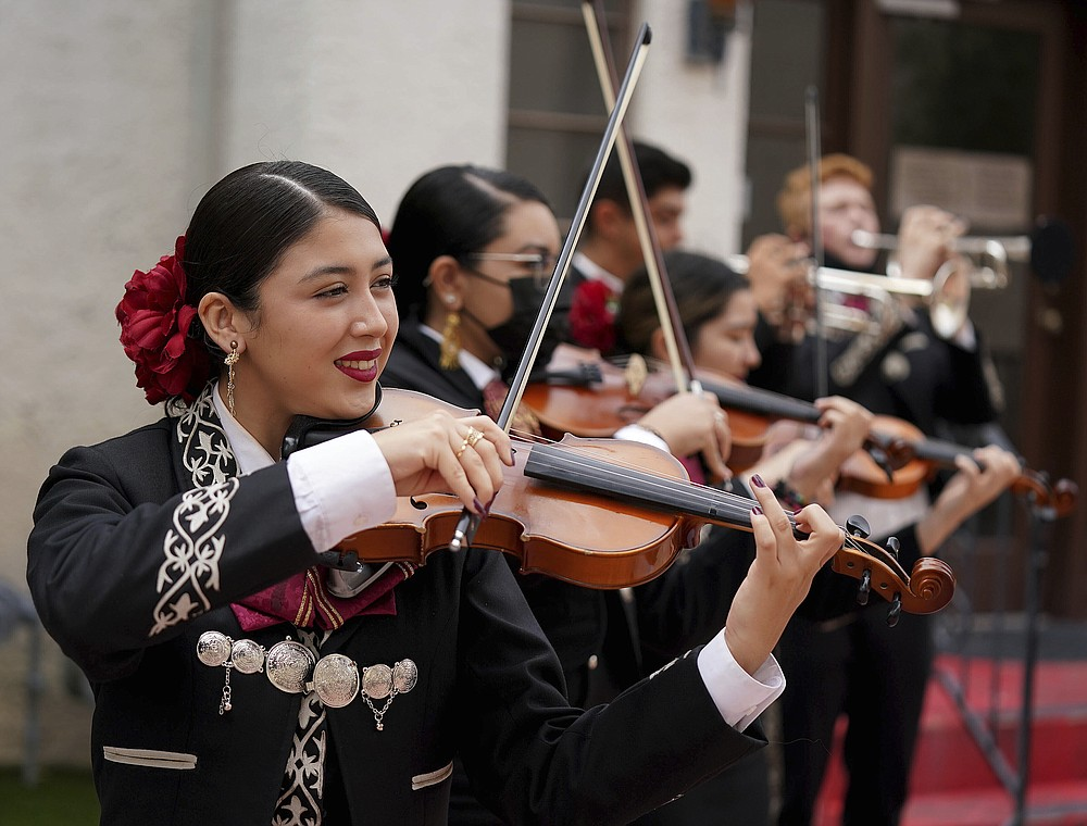 Alma Mccune 15, and fellow members of mariachi band Los Changuitos Feos (Ugly Little Monkeys) preform for parishioners after a morning Mass at St. Augustine Cathedral Sunday, Aug. 18, 2021 in downtown Tucson. (AP Photo/Darryl Webb)
