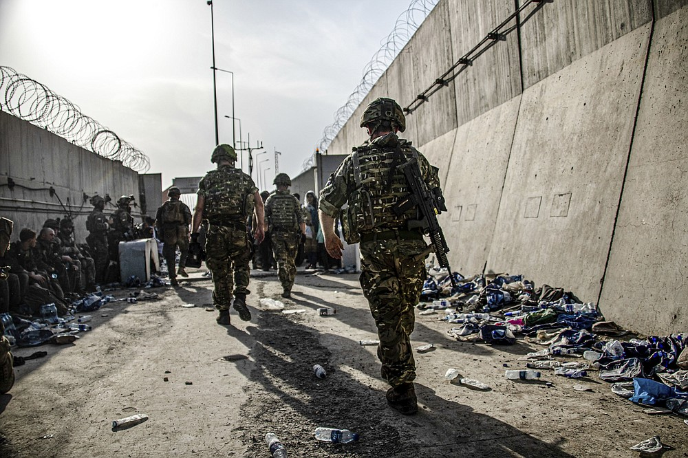 """In this photo issued by Britain's Ministry of Defence (MoD), showing members of UK Armed Forces who are working to evacuate entitled personnel from Afghanistan's Kabul airport, Monday Aug. 23, 2021.  Defence Secretary Ben Wallace has said the Kabul evacuation effort is """"down to hours now, not weeks"""" as he conceded Britain's involvement will end when the US leaves Afghanistan.  (LPhot Ben Shread/MoD via AP)"""