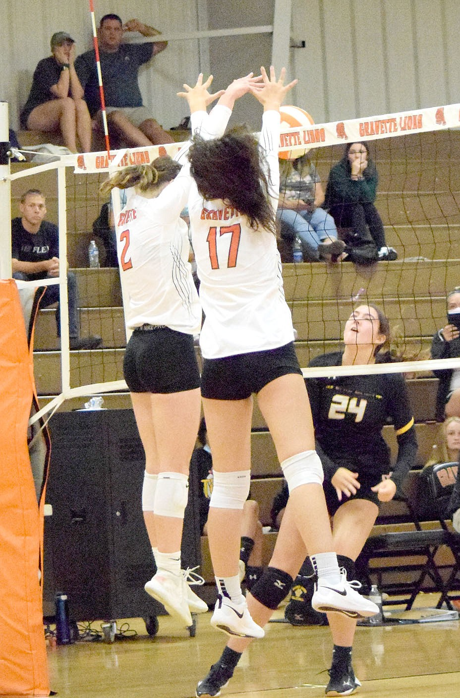 Westside Eagle Observer/MIKE ECKELS  Working together, Lady Lion Abby Smith (2) and Ella Pinches (17) deflect the ball back over the net into Lady Tiger territory during the second set of the Gravette-Prairie Grove varsity match at the Competition Gym in Gravette Thursday night. The Lady Lions took its second win of the 2021 season in three straight sets over the Lady Tigers.