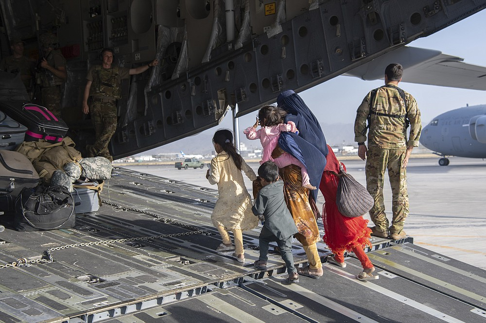 In this image provided by the U.S. Air Force, U.S. Air Force loadmasters and pilots assigned to the 816th Expeditionary Airlift Squadron, load people being evacuated from Afghanistan onto a U.S. Air Force C-17 Globemaster III at Hamid Karzai International Airport in Kabul, Afghanistan, Tuesday, Aug. 24, 2021. (Master Sgt. Donald R. Allen/U.S. Air Force via AP)