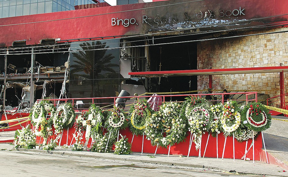 FILE - In this Aug, 27, 2011, file photo, a makeshift memorial of funeral wreaths line the circular driveway of the Casino Royale in Monterrey, Mexico. A surveillance tape showed eight or nine men arriving in four cars Thursday at the gambling house and setting fire to the building; trapping dozens of people inside and killing at least 52 people, mostly women. (AP Photo/Hans-Maximo Musielik, File)