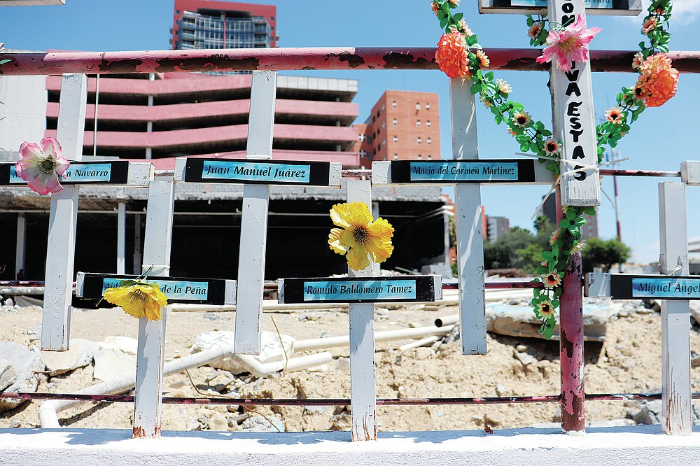 In front of the land occupied by the Casino Royale, relatives have installed a memorial to remember the victims of the Aug. 25, 2011 attack on the Casino Royale, in Monterrey, Mexico, Friday, Aug. 20, 2021. The dozens of white crosses bear the names of the deceased. (AP Photo/Marcos Martinez Chacon)