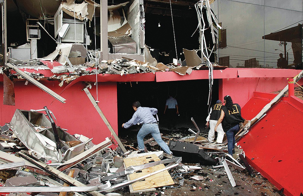 Investigators walk through debris of the charred Casino Royale after a deadly arson assault, in Monterrey, Mexico, Friday Aug. 26, 2011. A surveillance tape showed eight or nine men arriving in four cars Thursday at the casino and setting fire to the building, trapping dozens of people inside and killing at least 52 people. The attack was different than others in recent years in that the victims weren't cartel foot soldiers or migrants resisting forced recruitment by gangs. They were part of the middle class, working or gambling in an affluent part of a city that was once considered one of Mexico's safest. (AP Photo/Arnulfo Franco)