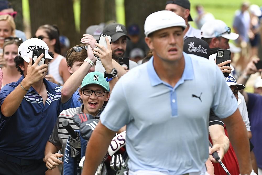 Los espectadores corren detrás de Bryson DeChambeau después de que lanzó desde el rough en el octavo hoyo en la tercera ronda del torneo de golf BMW Championship el sábado 28 de agosto de 2021, en Caves Valley Golf Club en Owings Mills, Maryland (AP Photo / Terrance Williams )