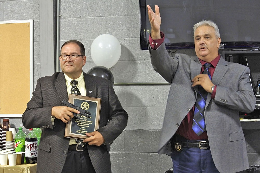 Jim Damante, the new sheriff of Crawford County, right, speaks while outgoing Sheriff Ron Brown, left, listens during the retirement party for Brown at the Crawford County Emergency Operations Center in Van Buren Tuesday.  (NWA Democrat-Gazette/Thomas Saccente)