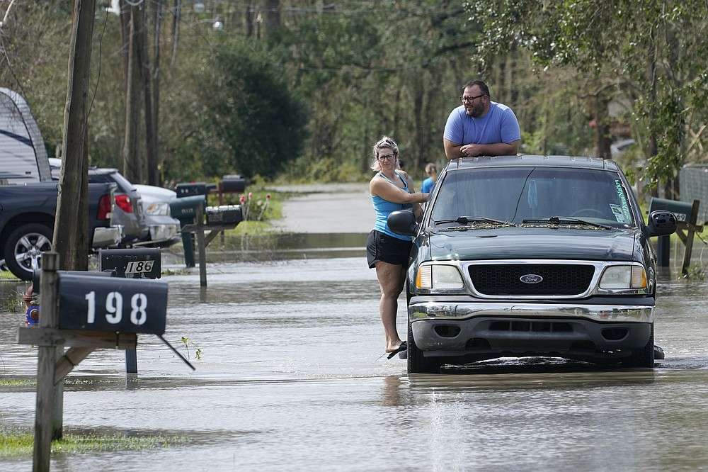 Alexis Hayes and her husband, Kristopher, get a ride out of a flooded neighborhood after Hurricane Ida moved through Monday, Aug. 30, 2021, in LaPlace, La. (AP Photo/Steve Helber)