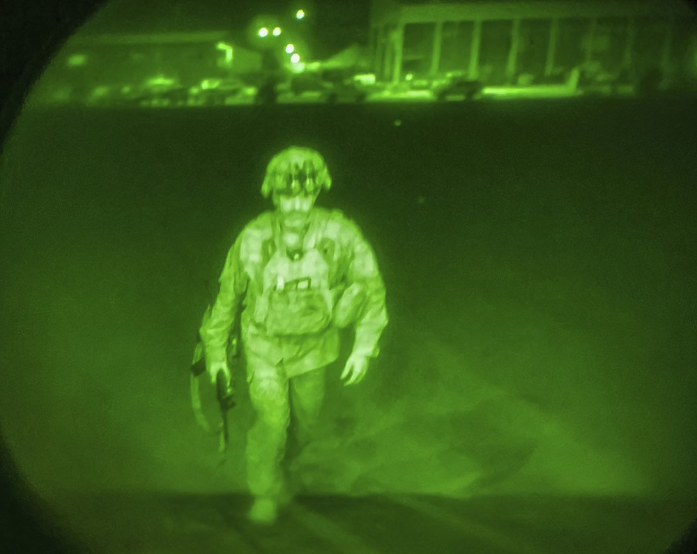 In this image made through a night vision scope and provided by U.S. Central Command, Maj. Gen. Chris Donahue, commander of the U.S. Army 82nd Airborne Division, XVIII Airborne Corps, boards a C-17 cargo plane at the Hamid Karzai International Airport in Kabul, Afghanistan, Monday, Aug. 30, 2021, as the final American service member to depart Afghanistan. (U.S. Central Command via AP)