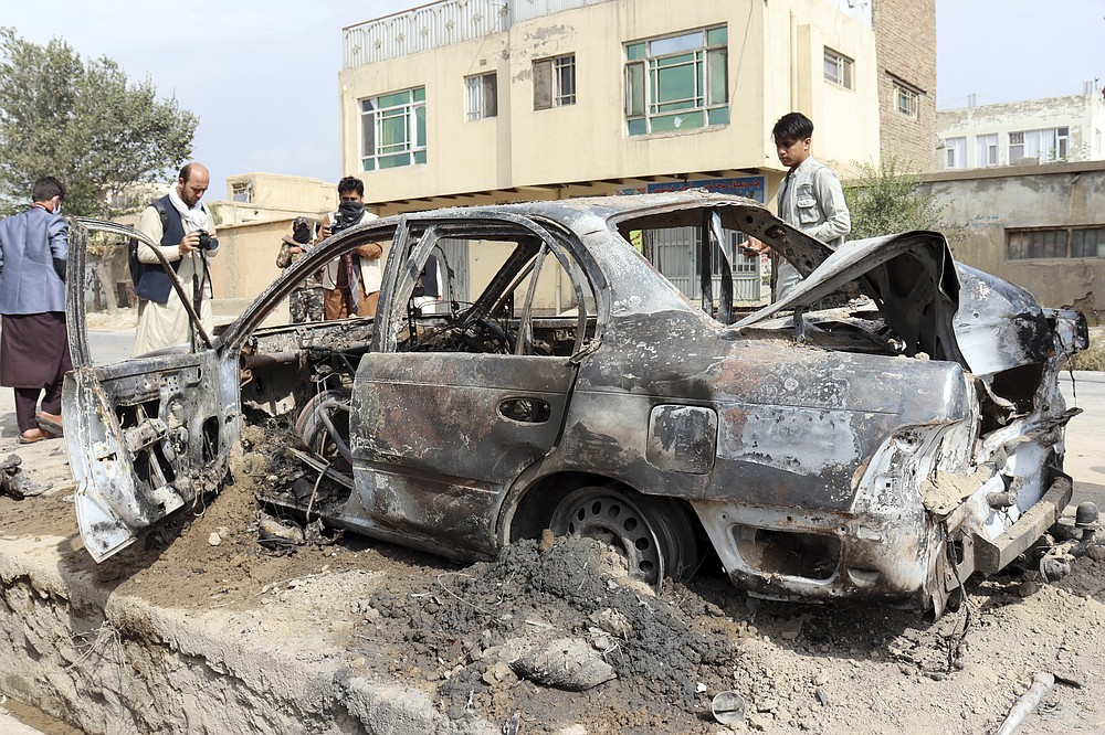 Journalists take photos of a vehicle damaged by a rocket attack in Kabul, Afghanistan, Monday, Aug. 30, 2021. Rockets struck a neighborhood near Kabul's international airport on Monday amid the ongoing U.S. withdrawal from Afghanistan. It wasn't immediately clear who launched them. (AP Photo/Khwaja Tawfiq Sediqi)