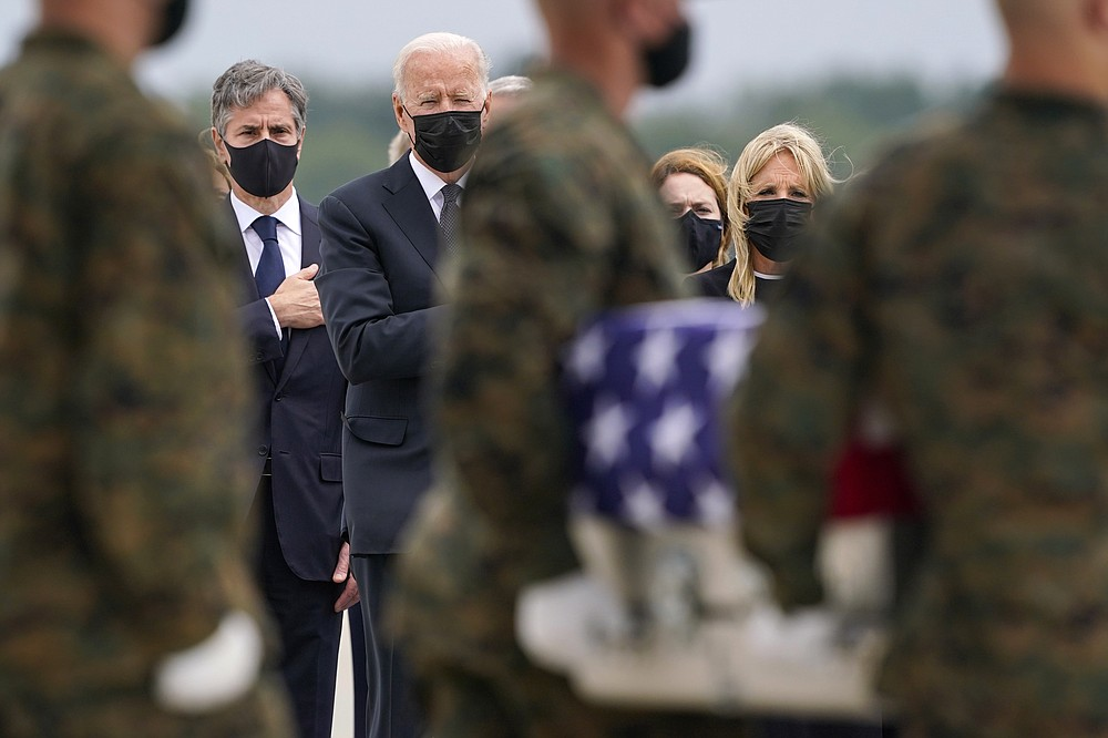President Joe Biden, first lady Jill Biden, and Secretary of State Antony Blinken look on as as a carry team moves a transfer case with the remain of Marine Corps Cpl. Humberto A. Sanchez, 22, of Logansport, Ind., during a casualty return at Dover Air Force Base, Del., Sunday, Aug. 29, 2021, for the 13 service members killed in the suicide bombing in Kabul, Afghanistan, on Aug. 26. (AP Photo/Carolyn Kaster)