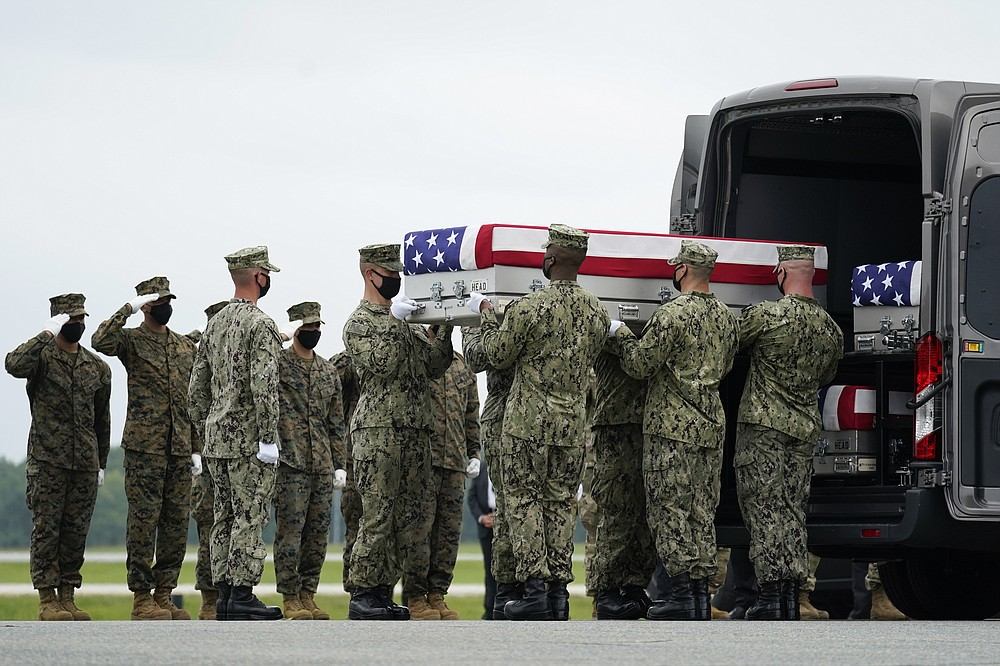 A carry team loads a transfer case with the remain of Navy Corpsman Maxton W. Soviak, 22, of Berlin Heights, Ohio, into a transfer vehicle during a casualty return at Dover Air Force Base, Del., Sunday, Aug. 29, 2021, for the 13 service members killed in the suicide bombing in Kabul, Afghanistan, on Aug. 26. (AP Photo/Carolyn Kaster)
