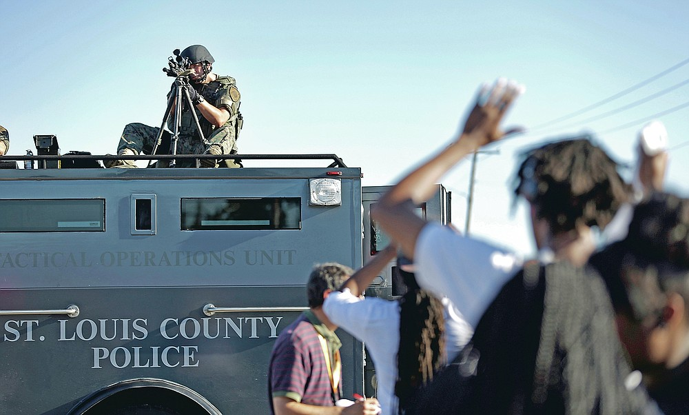 ADVANCE FOR PUBLICATION ON FRIDAY, SEPT. 10, AND THEREAFTER - FILE - In this Wednesday, Aug. 13, 2014 file photo, a member of the St. Louis County Police Department points his weapon in the direction of a group of protesters in Ferguson, Mo. On Saturday, Aug. 9, 2014, a white police officer fatally shot Michael Brown, a Black teenager, in the St. Louis suburb. (AP Photo/Jeff Roberson, File)