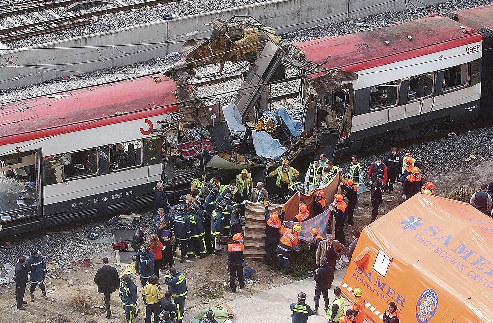 ADVANCE FOR PUBLICATION ON FRIDAY, SEPT. 10, AND THEREAFTER - FILE - In this March 11, 2004 file photo, rescue workers cover bodies alongside a bomb-damaged passenger train, following a number of explosions in Madrid, Spain, which killed more than 170 rush-hour commuters and wounded more than 500 in Spain's worst terrorist attack ever. An Al-Qaida-linked group that claimed responsibility for the Madrid train bombings warned European nations that they have only two weeks to withdraw troops from Iraq or face the consequences, a pan-Arab newspaper reported Friday, July 2, 2004. (AP Photo/Paul White, File)