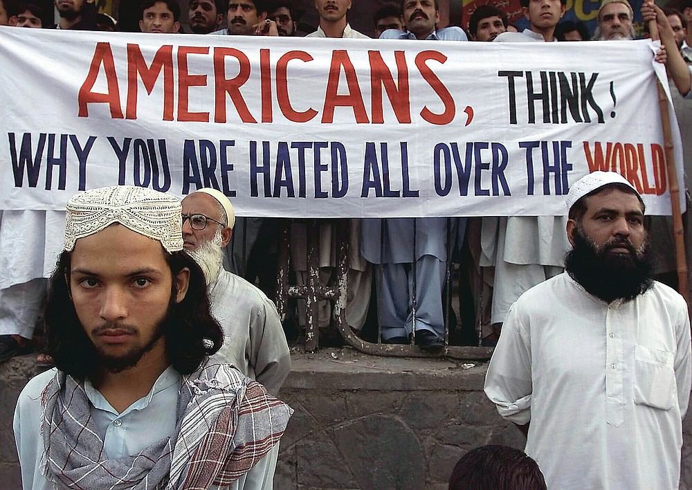 """ADVANCE FOR PUBLICATION ON FRIDAY, SEPT. 10, AND THEREAFTER - FILE - In this Saturday, Sept. 15, 2001 file photo, activists of Pakistan militant religious parties stand with a banner which reads, """"Americans, think why you are hated all over the world,"""" during a rally in Islamabad, Pakistan to condemn possible U.S. attacks on neighboring Afghanistan. People are fearing here that the U.S. will attack on Afghanistan in retaliation of the attacks in New York and Washington earlier in the week. (AP Photo/B.K. Bangash, File)"""