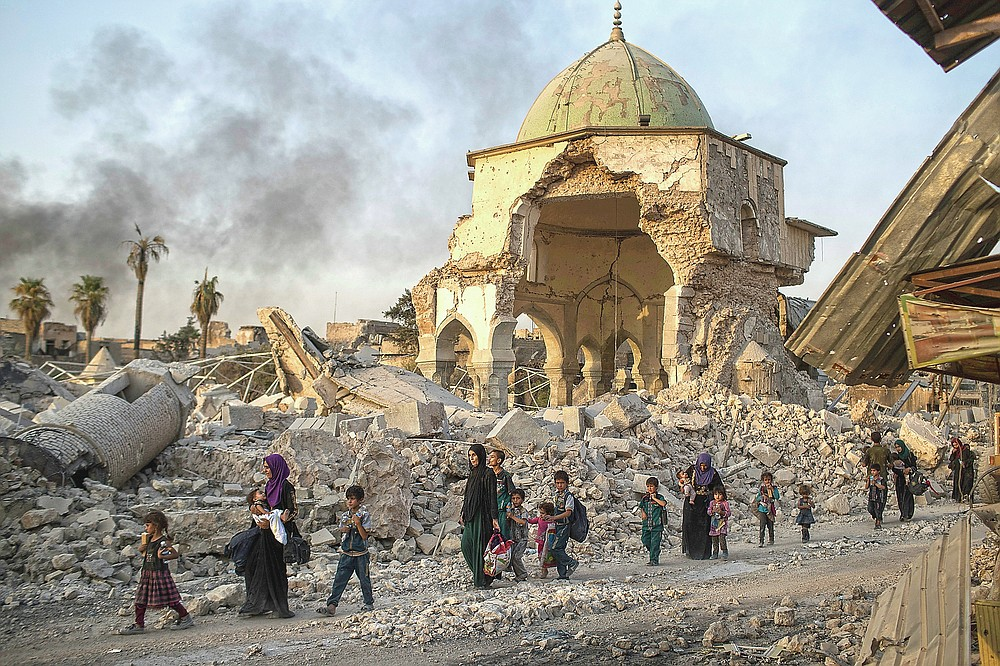 ADVANCE FOR PUBLICATION ON FRIDAY, SEPT. 10, AND THEREAFTER - FILE - In this Tuesday, July 4, 2017 file photo, fleeing Iraqi civilians walk past the heavily damaged al-Nuri mosque as Iraqi forces continue their advance against Islamic State militants in the Old City of Mosul, Iraq. As Iraqi forces continued to advance on the last few hundred square kilometers of Mosul held by the Islamic State group, the country's Prime Minister said Tuesday the gains show Iraqis reject terrorism. (AP Photo/Felipe Dana, File)