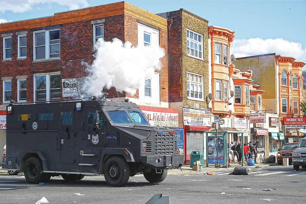 ADVANCE FOR PUBLICATION ON FRIDAY, SEPT. 10, AND THEREAFTER - FILE - In this May 31, 2020 file photo, police deploy tear gas to disperse a crowd during a protest in Philadelphia over the death of George Floyd. Floyd died May 25, 2020 after he was pinned at the neck by a white Minneapolis police officer. (AP Photo/Matt Rourke, File)
