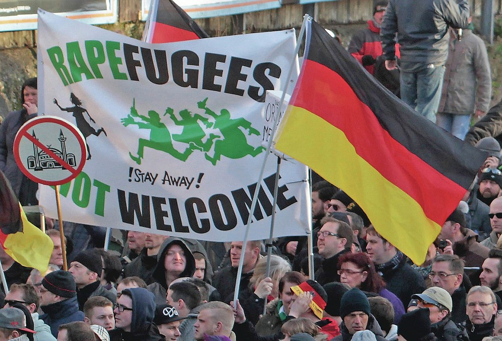 """ADVANCE FOR PUBLICATION ON FRIDAY, SEPT. 10, AND THEREAFTER - FILE - In this Saturday Jan. 9, 2016 file photo, right-wing demonstrators hold a sign which reads, """"Rapefugees not welcome - !Stay away!"""" and a sign with a crossed out mosque as they march in Cologne, Germany. Women's rights activists, far-right demonstrators and left-wing counter-protesters all took to the streets of Cologne on Saturday in the aftermath of a string of New Year's Eve sexual assaults and robberies in Cologne blamed largely on foreigners. (AP Photo/Juergen Schwarz, File)"""