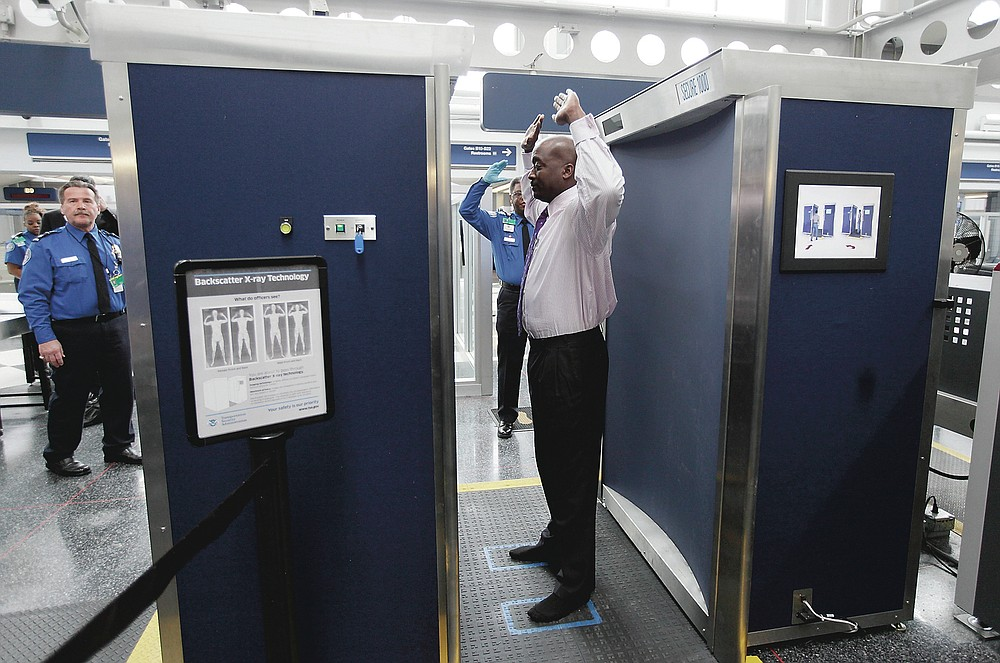 ADVANCE FOR PUBLICATION ON FRIDAY, SEPT. 10, AND THEREAFTER - FILE - In this March 15, 2010 file photo, a volunteer passes through the first full body scanner installed at O'Hare International Airport in Chicago. The technology produces a cartoon-like outline rather than naked images of passengers by using X-rays. (AP Photo/M. Spencer Green, File)
