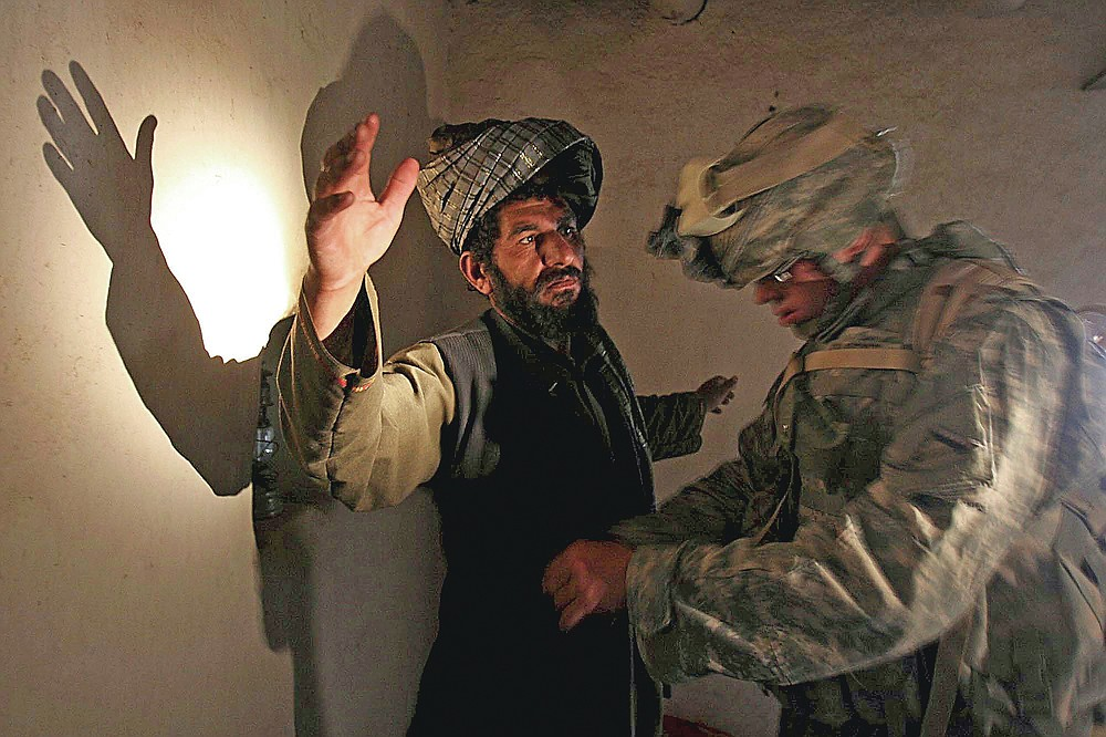 ADVANCE FOR PUBLICATION ON FRIDAY, SEPT. 10, AND THEREAFTER - FILE - In this Monday, April 2, 2007 file photo, a U.S. soldier of B company, 4th Infantry Regiment frisks an afghan man in his house during a search operation in Sinan village in Zabul province, southeastern Afghanistan. (AP Photo/Rafiq Maqbool, File)