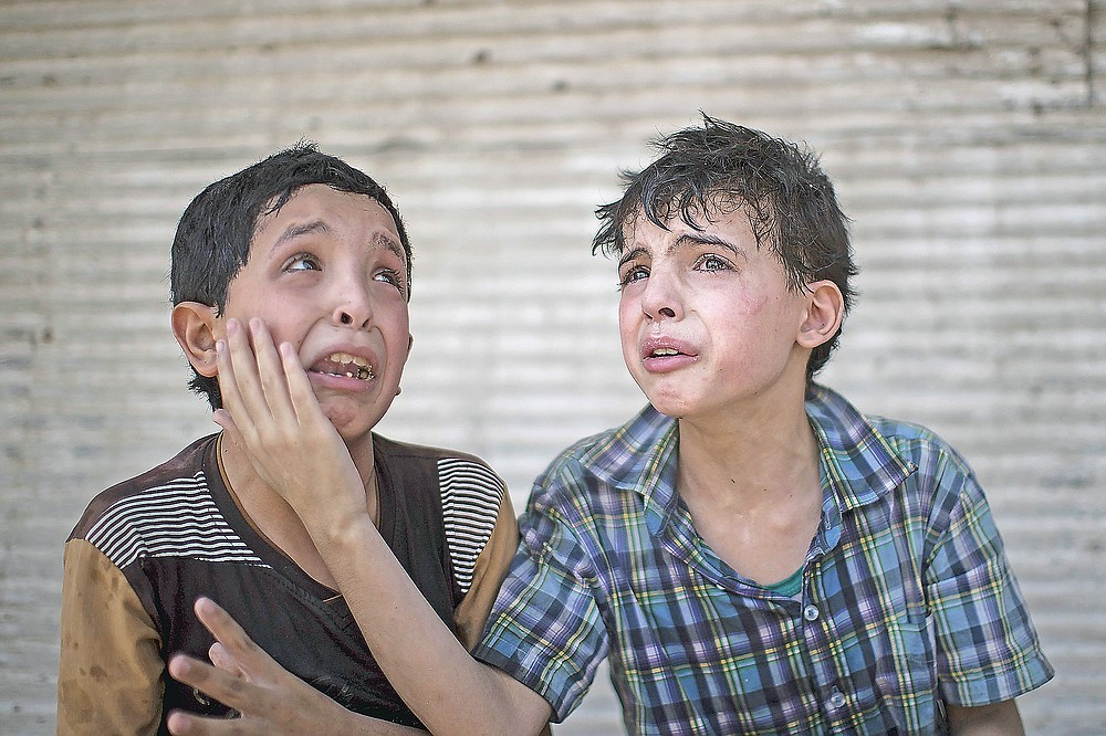 ADVANCE FOR PUBLICATION ON FRIDAY, SEPT. 10, AND THEREAFTER - FILE - In this Saturday, June 24, 2017 file photo, Zeid Ali, 12, left, and Hodayfa Ali, 11, comfort each other after their house was hit and collapsed during fighting between Iraqi forces and Islamic State militants in Mosul, Iraq. The Ali cousins said some of their family members are still under the rubble. (AP Photo/Felipe Dana, File)