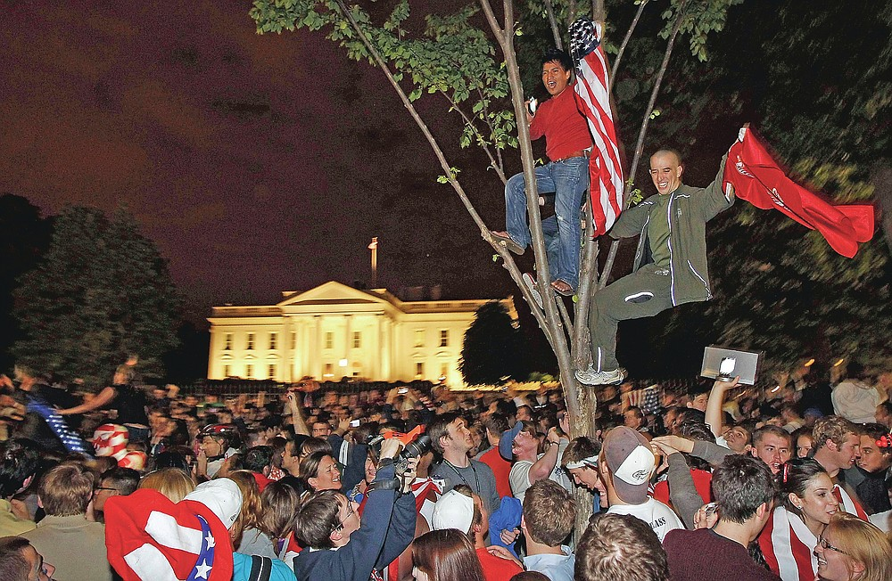 ADVANCE FOR PUBLICATION ON FRIDAY, SEPT. 10, AND THEREAFTER - FILE - In this Monday, May 2, 2011 file photo, crowds climb trees and celebrate in Lafayette Park in front of the White House in Washington after President Barack Obama announced that Osama bin Laden had been killed. (AP Photo/Charles Dharapak, File)