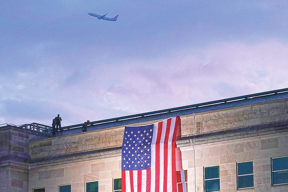 ADVANCE FOR PUBLICATION ON FRIDAY, SEPT. 10, AND THEREAFTER - FILE - In this Friday, Sept. 11, 2020 file photo, a plane takes off from Washington Reagan National Airport as a large U.S. flag is unfurled at the Pentagon ahead of ceremonies at the National 9/11 Pentagon Memorial to honor the 184 people killed in the 2001 terrorist attack on the Pentagon, in Washington, Friday, Sept. 11, 2020. (AP Photo/J. Scott Applewhite, File)