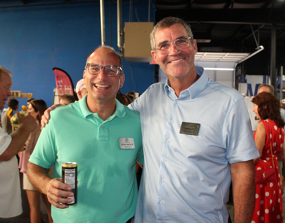 John Mauck (left) and Ted Fox, Boys & Girls Club board members, help the nonprofit organization welcome supporters to Sip & Savor on Aug. 19. (NWA Democrat-Gazette/Carin Schoppmeyer)
