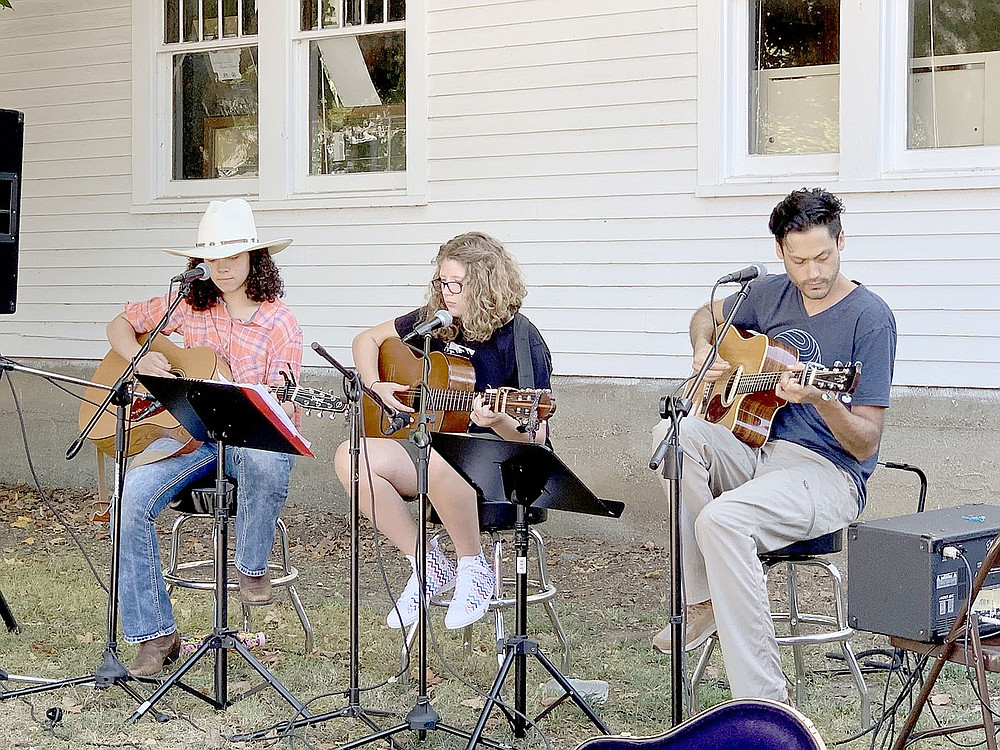 LYNN KUTTER ENTERPRISE-LEADER Patience Remington, of Lincoln, left, Peyton Orona of Prairie Grove and Jacob Phaneuf, owner of Inside Out Studio in Farmington, play at the Prairie Grove Farmers Market. The two girls are part of a program called Roots Music, sponsored through the studio by Historic Cane Hill.