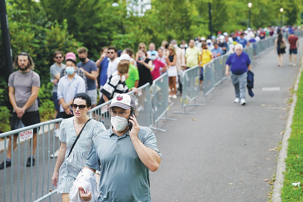 Tennis fans line up outside the Billie Jean King National Tennis Center for the first round of the US Open tennis championships on Monday, August 30, 2021, in New York City.  (AP Photo / John Minchillo)