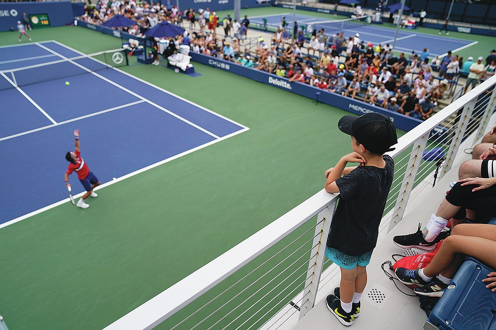 Tennis fans watch Ricardas Berankis of Lithuania serve Diego Schwartzman of Argentina in the first round of the US Open tennis championships on Monday, August 30, 2021, in New York City.  (AP Photo / John Minchillo)