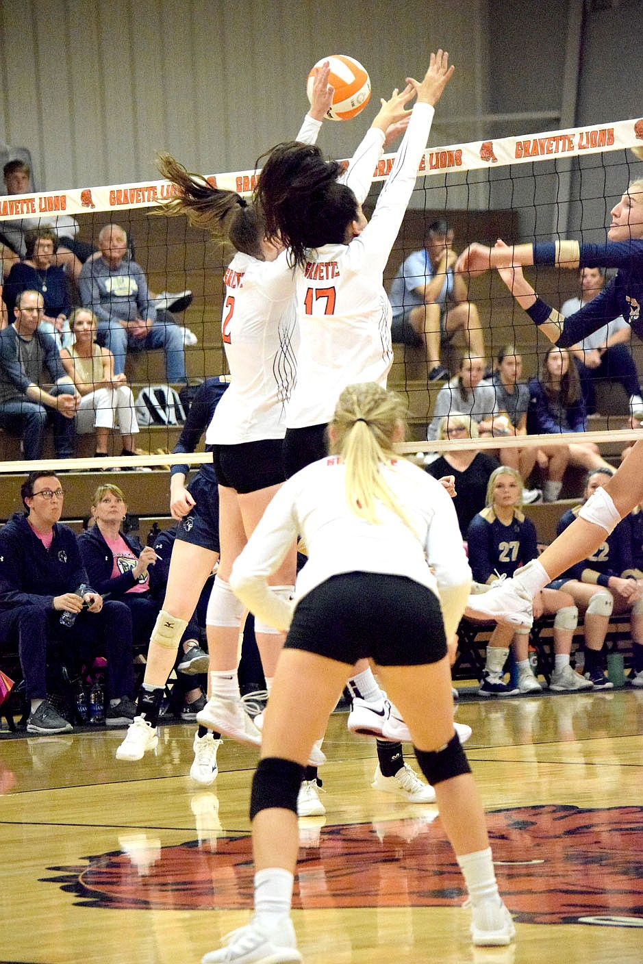 Westside Eagle Observer/MIKE ECKELS Working as a team, Lady Lions Abby Smith (2) and Ella Pinches (17) deflect a hit back into Lady Saint territory during the third set of the Gravette-Shiloh Christian varsity volleyball match in Gravette Thursday night.