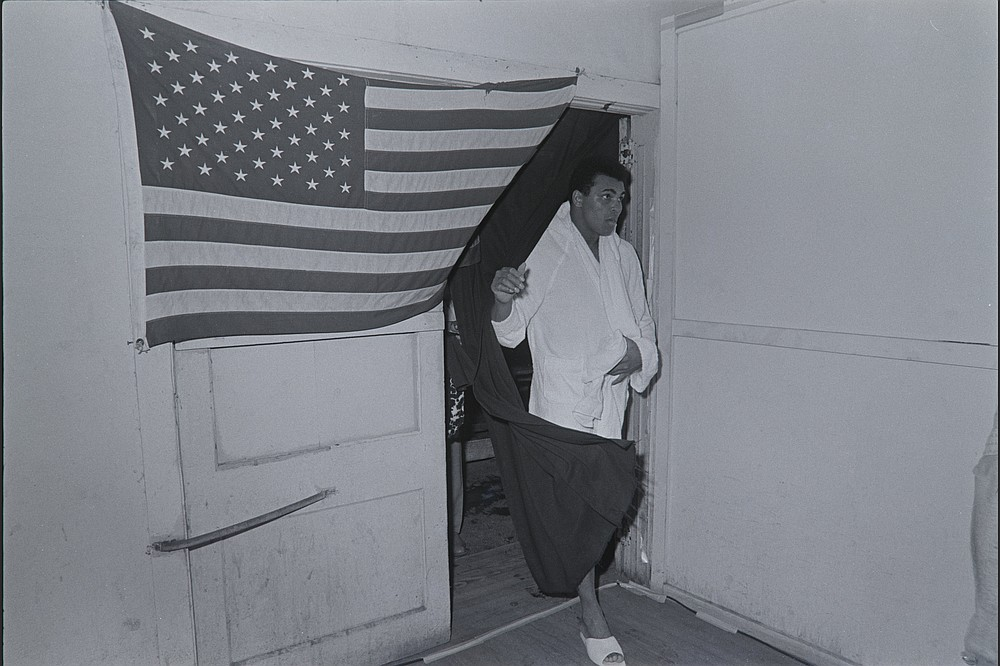 Muhammad Ali comes through a doorway draped in a United States flag at the Fifth Street Gym in Miami on Feb. 25, 1971. (Courtesy of PBS)