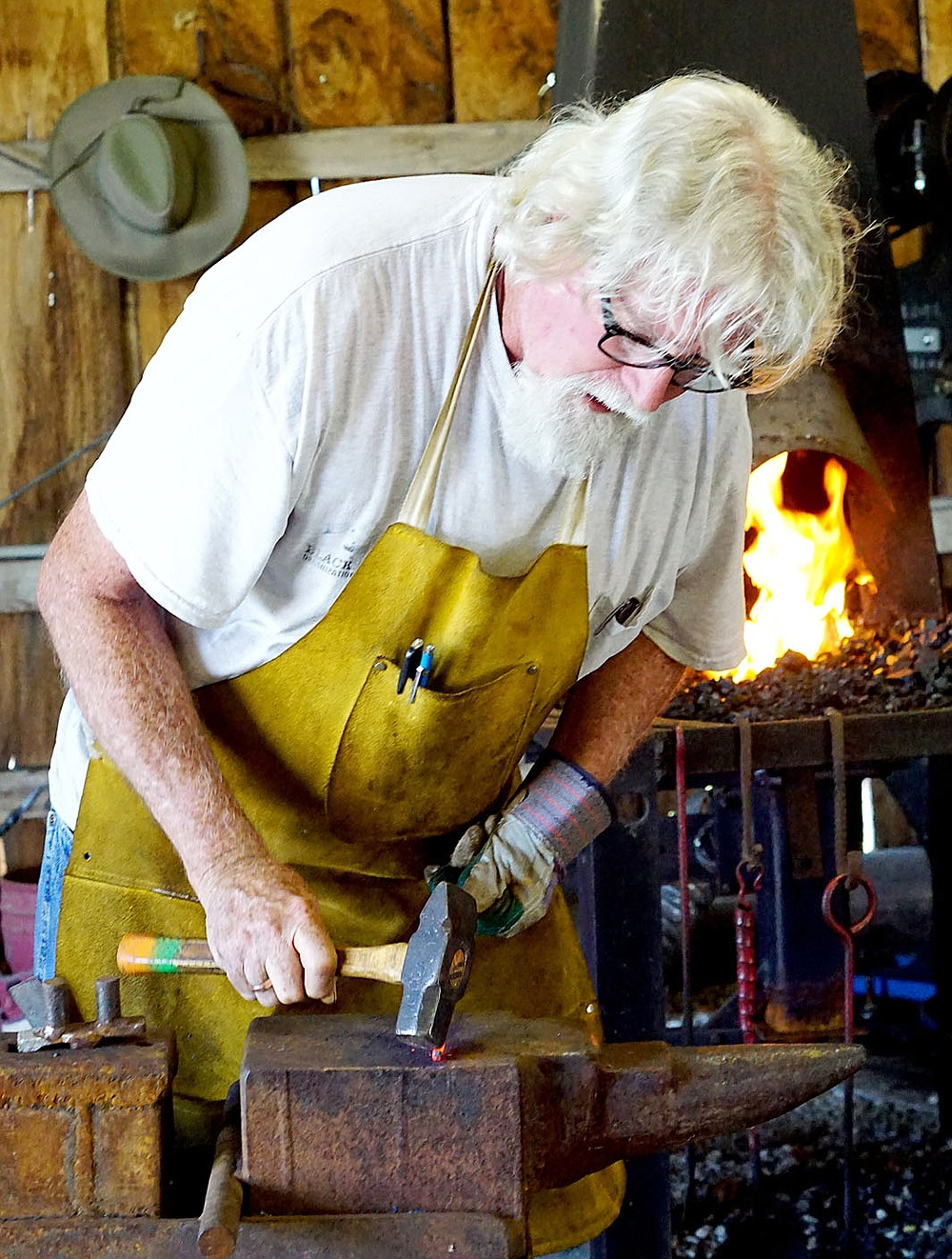 Westside Eagle Observer/RANDY MOLL Steve Low, of Gentry, bends a piece of hot iron on Friday, Sept. 6, 2019, to make a handle for a utensil he is building. Low was working at a forge and anvil in the blacksmith shop at the Tired Iron of the Ozarks showgrounds in Gentry during the fall show.