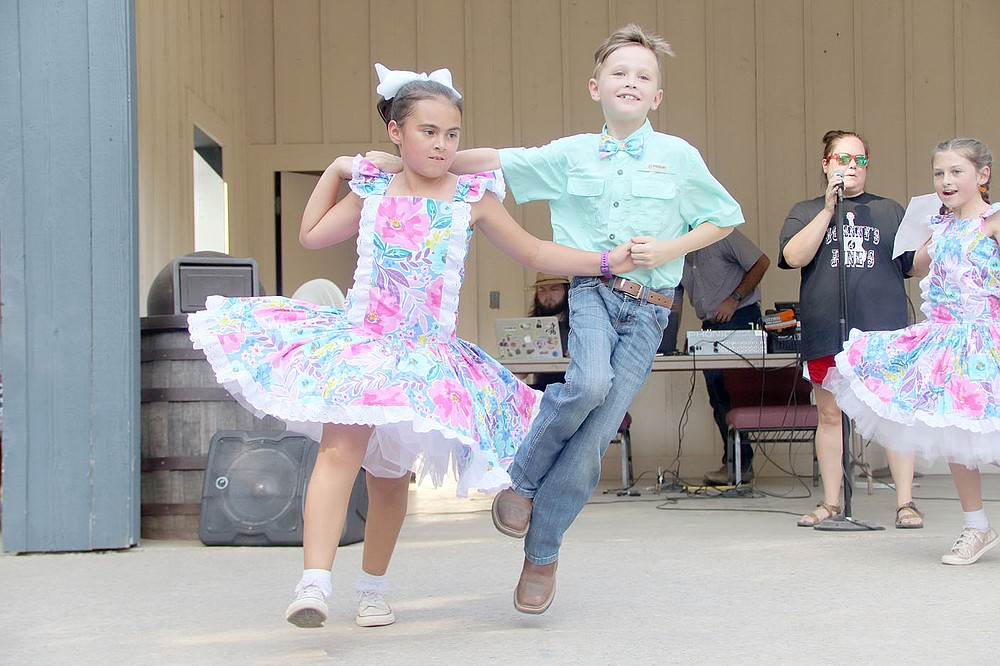 Amelia Hall and Declan Sharp with the exhibition square dance group Johnny's and June's take their turn on the dance floor Saturday at the amphitheater at Prairie Grove Battlefield State Park.